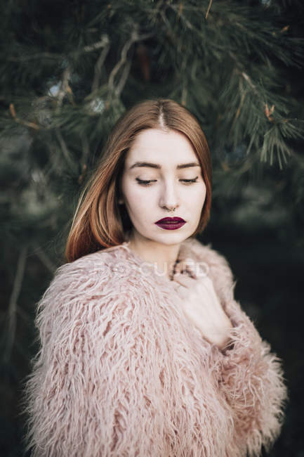 Sensual young girl with bright lips posing by fir branches and looking down — Stock Photo