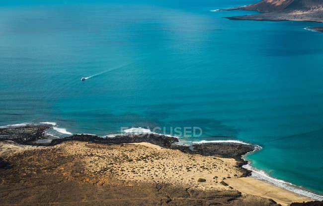 Vue aérienne de petit bateau flottant dans l'océan bleu — Photo de stock