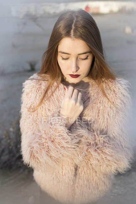 Sensual stylish model with bright lips posing in fur coat and looking down — Stock Photo