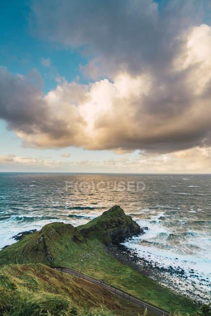 Idílica vista al verde roca costera en playa en día soleado - foto de stock
