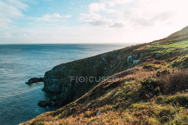 Calm ocean and green hill on sunny day — Stock Photo
