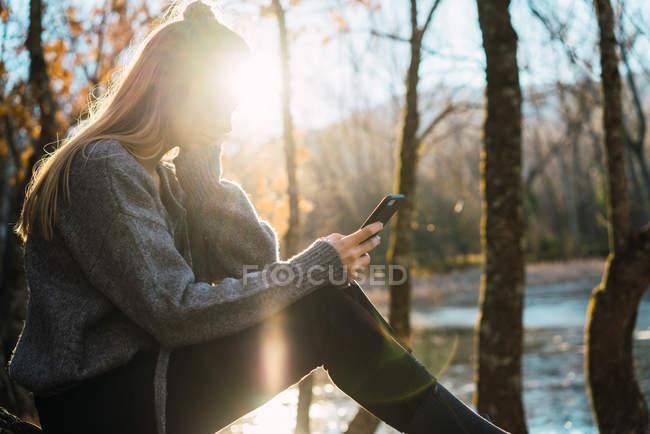 Vue latérale de la femme ensoleillée naviguant smartphone dans les bois d'automne — Photo de stock