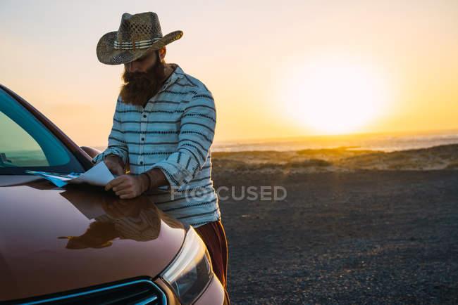 Fiducioso viaggiatore lettura mappa sul cofano dell'automobile al litorale — Foto stock
