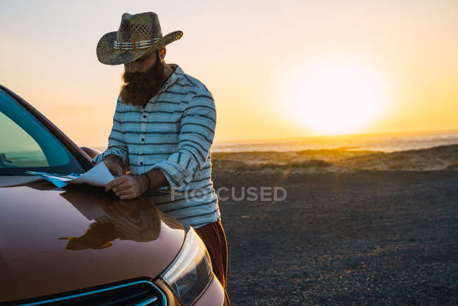 Confident traveler reading map on car bonnet at shoreline — Stock Photo