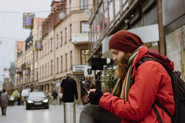 Vista laterale dell'uomo barbuto usando lo smartphone in città — Foto stock