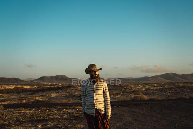 Barbudo con sombrero posando en el valle de arena y mirando hacia otro lado - foto de stock