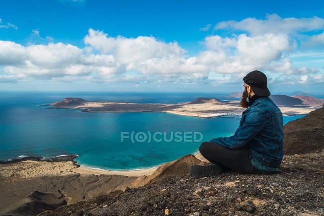 Вид сзади человека, сидящего на береговой линии и смотрящего в сторону моря — стоковое фото