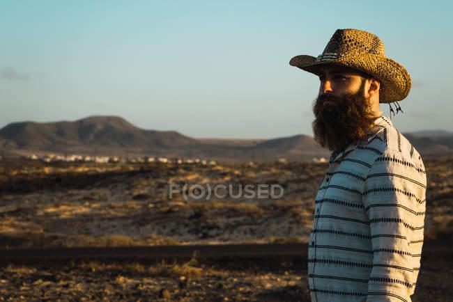 Vista lateral del hombre barbudo en sombrero en valle seco - foto de stock