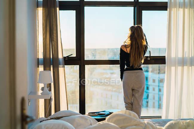 Vista posteriore della giovane ragazza con i capelli lunghi in posa vicino alla finestra a casa — Foto stock