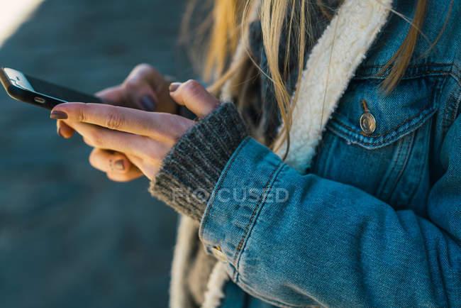 Обрезать женские руки печатая на смартфоне — стоковое фото