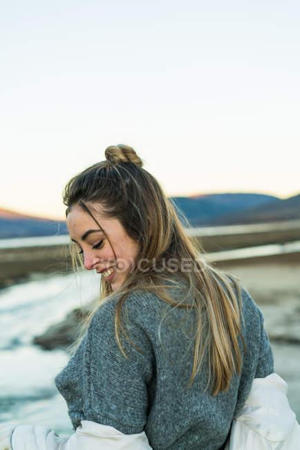 Vista traseira da mulher sorridente na camisola olhando por cima do ombro para baixo — Fotografia de Stock