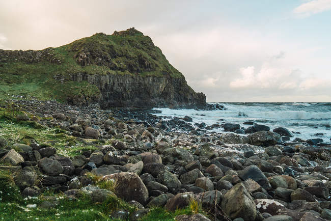 Idyllic view of stones and green hill at seaside — Stock Photo