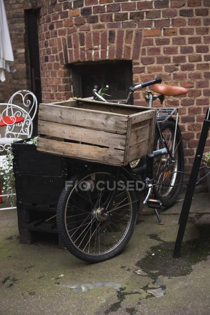 Bicicleta aparcada con caja de madera como el tronco de frente en la calle. - foto de stock