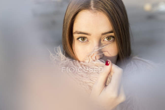 Portrait of stylish girl cuddling on cozy coat and looking at camera — Stock Photo