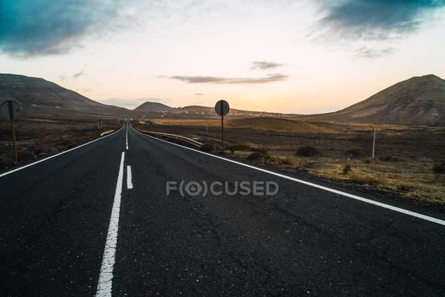 Strada asfaltata lunga scappando tra appartamenti e colline — Foto stock
