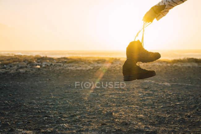 Crop hand showing trekking boots in sunlight — Stock Photo