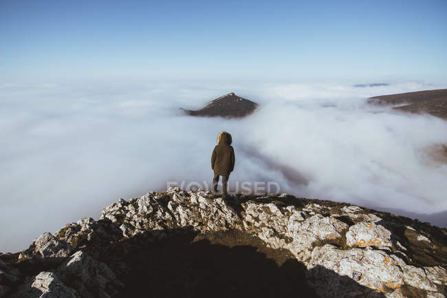 Rear view of man on rocky cliff against scenic cloudscape — Stock Photo