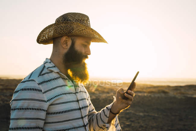 Vista lateral del hombre barbudo en el teléfono inteligente de navegación sombrero - foto de stock
