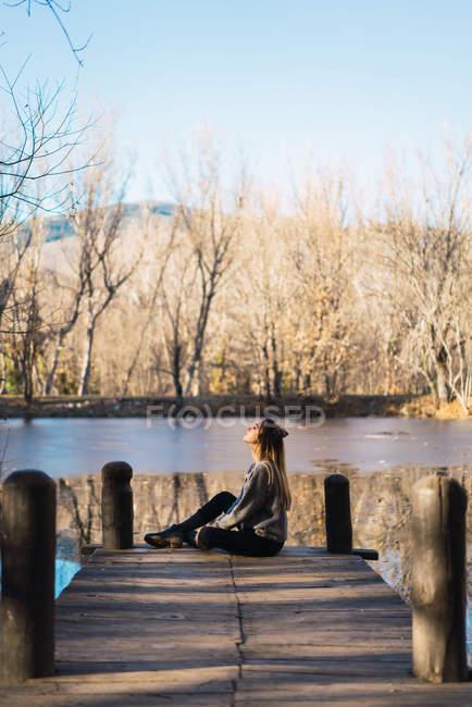 Seitenansicht der Träumende Frau sitzt am Holzsteg mit See in Abfallzeit auf Hintergrund. — Stockfoto