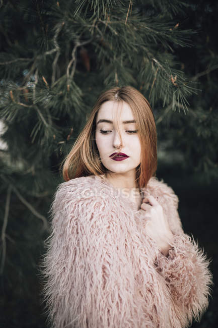 Sensual young girl with bright lips posing by fir branches and looking away — Stock Photo
