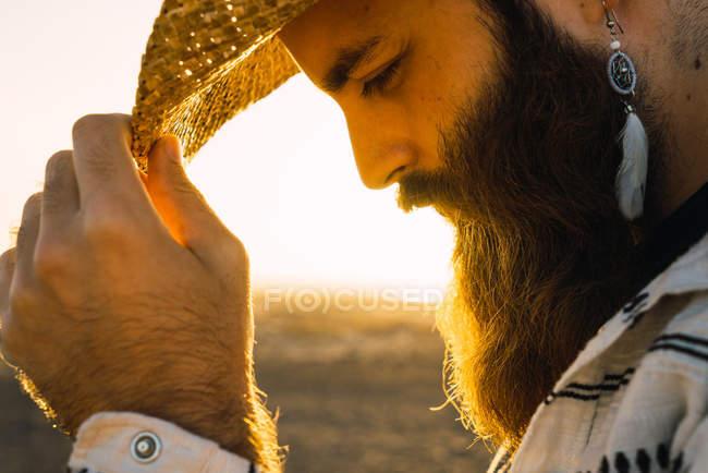 Hombre barbudo con sombrero de paja y arete de plumas posando contra la luz del sol - foto de stock