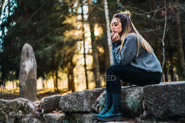 Side view of pensive girl sitting on stone in woods — Stock Photo