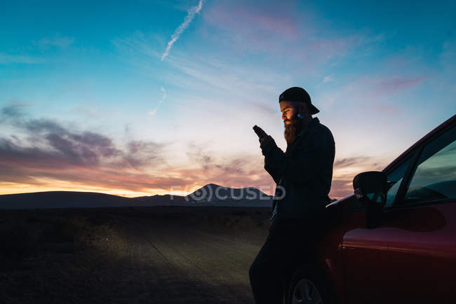 Side view of tourist leaning on car and browsing smartphone at countryside in dusk — Stock Photo