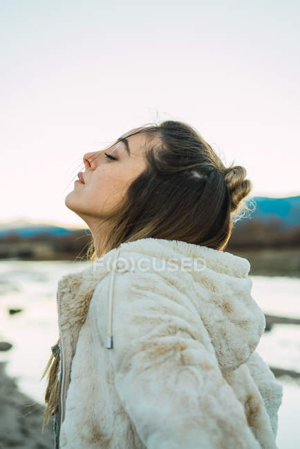 Side view of woman enjoying nature and freedom with eyes closed — Stock Photo