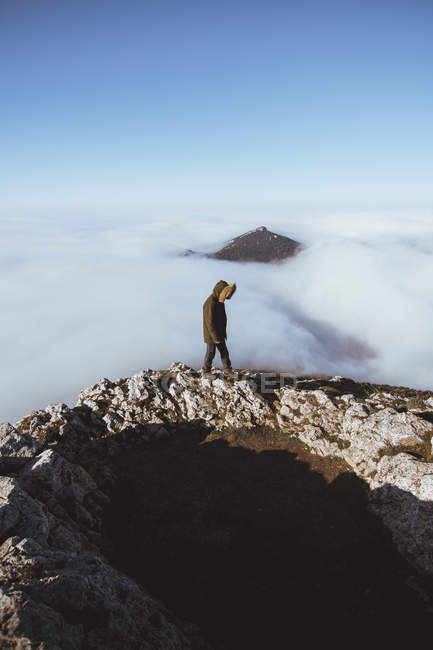 Man on walking rocky cliff in clouds against mountain peak in fog — Stock Photo