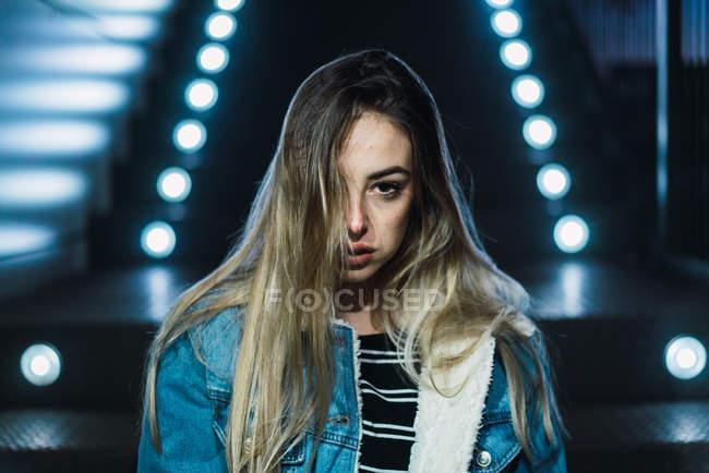 Портрет молодої жінки, дивлячись серйозно камери на фоні сходи з неонові світла. — стокове фото