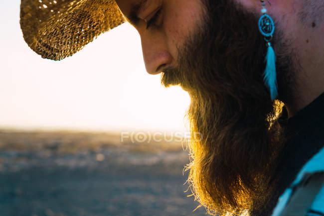 Crop hombre barbudo con pendiente y sombrero contra la luz del sol - foto de stock