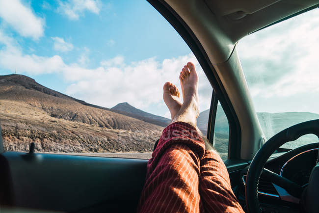 Crop male feet sticking out of car window on background of mountain valley in sunlight. — Stock Photo