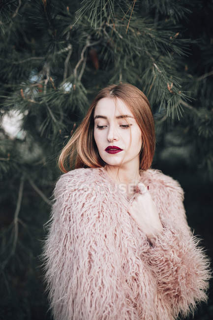Sensual young girl with bright lips posing by fir branches — Stock Photo