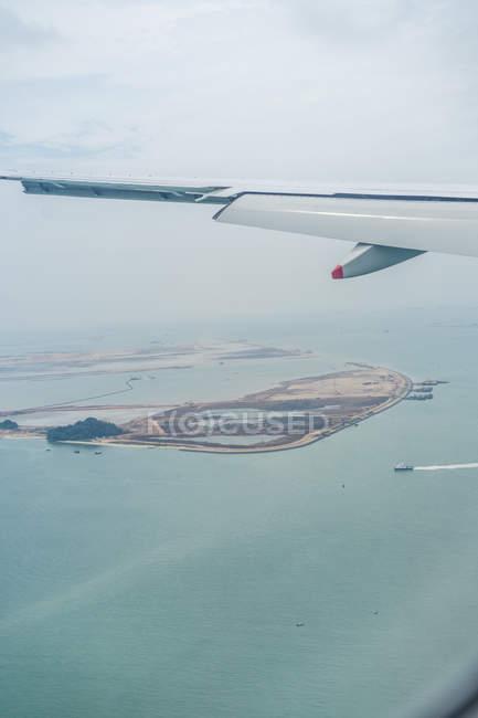 Ala de avión contra isla en océano turquesa - foto de stock