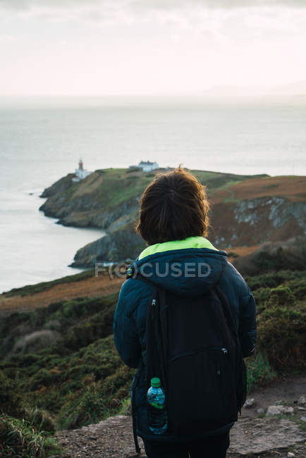 Rear view of man with backpack standing on coastal hill — Stock Photo