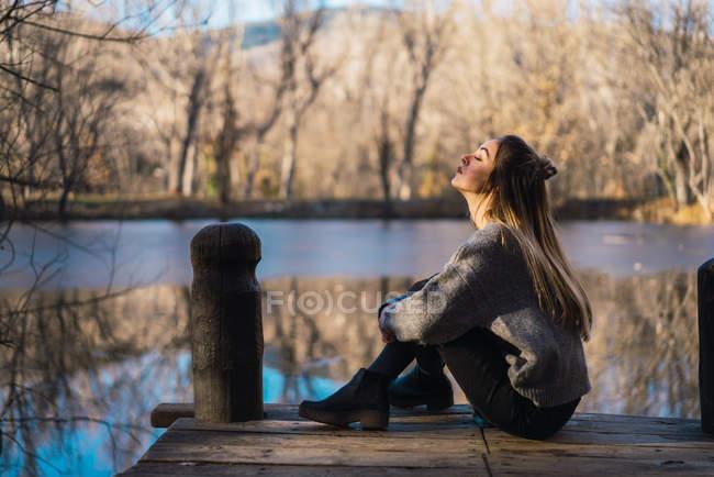 Vue latérale de la femme assise sur la jetée au-dessus de l'étang automnal — Photo de stock