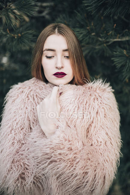 Sensual stylish model with bright lips looking down on background of fir tree — Stock Photo