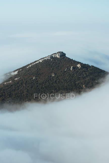 Tir panoramique du sommet de la montagne dans les nuages épais — Photo de stock