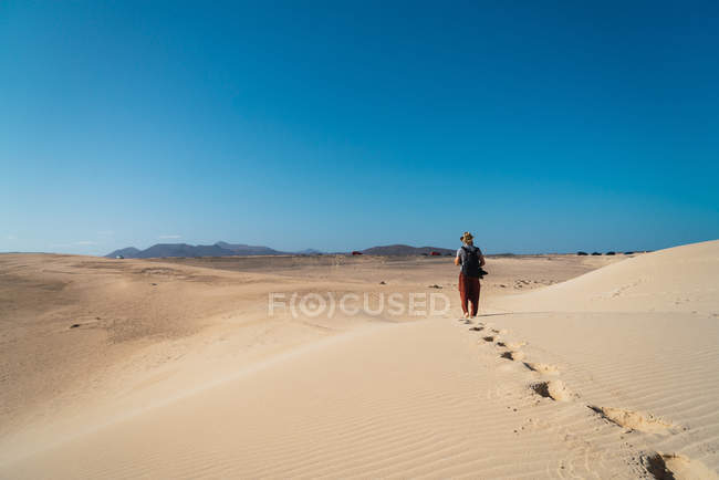 Back view of man with backpack exploring endless sandy terrains in sunlight. — Stock Photo