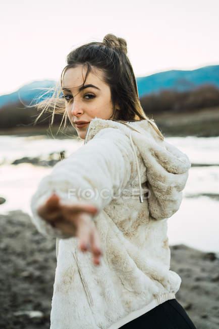 Портрет женщины глядя через плечо и outstretching руку на камеру — стоковое фото