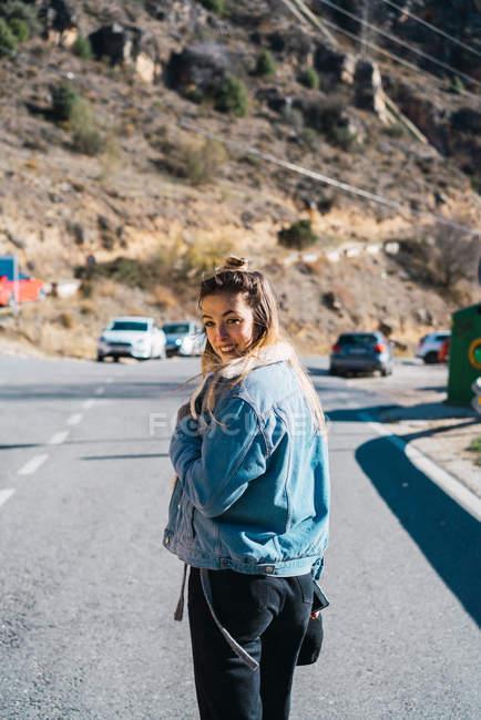 Вид случайных женщина в джинсовой куртке сзади на проезжую часть, глядя на камеру через плечо и улыбается — стоковое фото