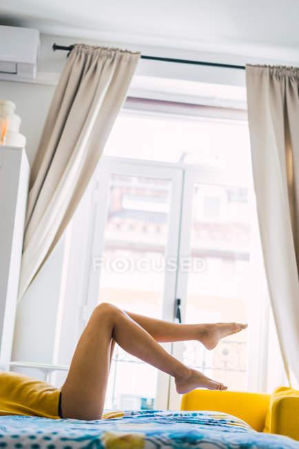 Обтинання спокусливі жінки, лежачи на ліжку у себе вдома — стокове фото
