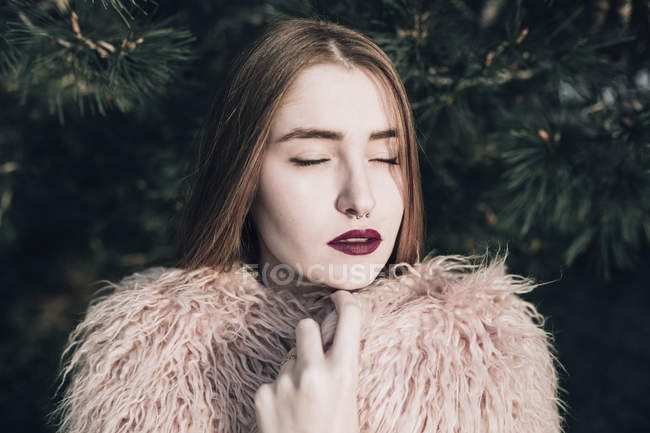 Sensual stylish girl with bright lips posing by fir branches with eyes closed — Stock Photo