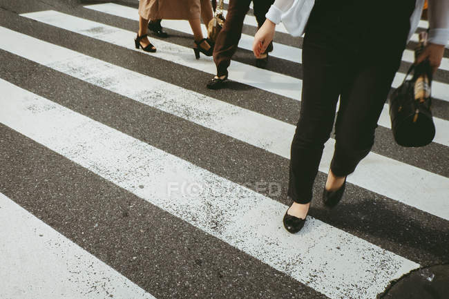 Low section of people walking on crosswalk at street. — Stock Photo