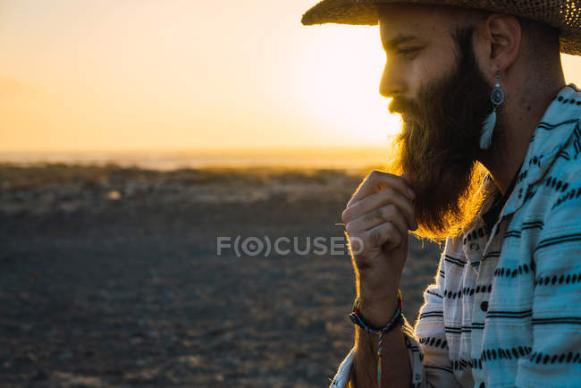 335d78a9c97 Side view of pensive bearded man wearing accessories and cowboy hat posing  in sunset on beach