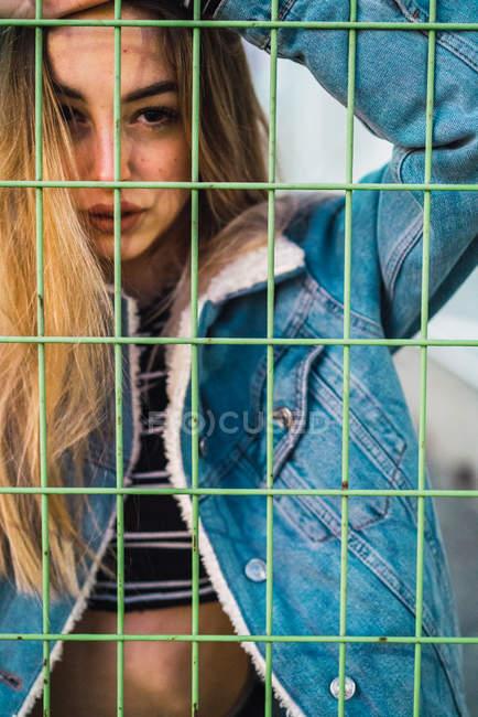 Portrait de jeune fille blonde provocante en denim regardant la caméra et derrière le métal net. — Photo de stock