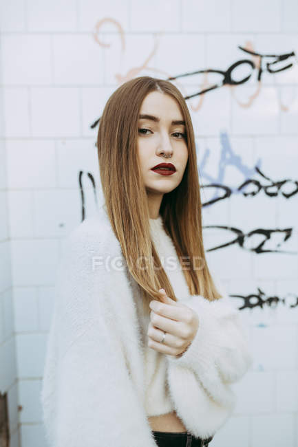 Young girl in cozy sweater posing on background of grungy wall — Stock Photo