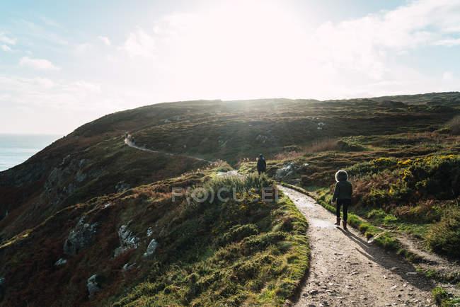 Vue arrière de touristes marchant sur la colline ensoleillée de la côte — Photo de stock