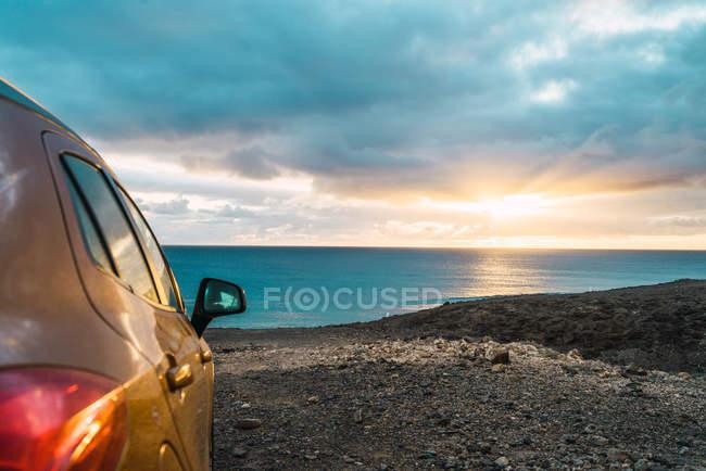 Обтинання автомобіля на скелястому shoreline океану — стокове фото