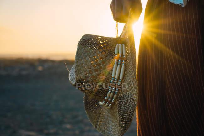 Ernte Schuss der männlichen holding Cowboyhut Stroh und im Sonnenuntergang Sonne am Ufer stehen. — Stockfoto